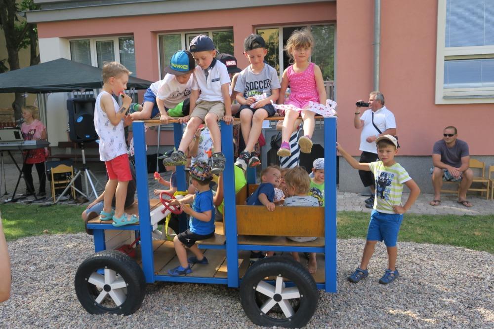 Děti sedí na autíčku.