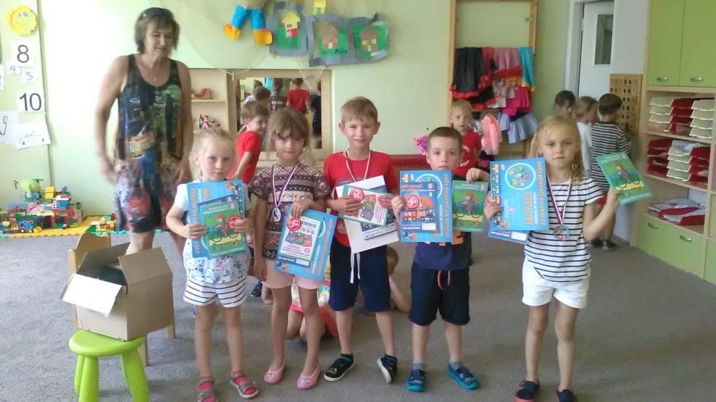Děti stojí a ukazují medaile a diplomy.