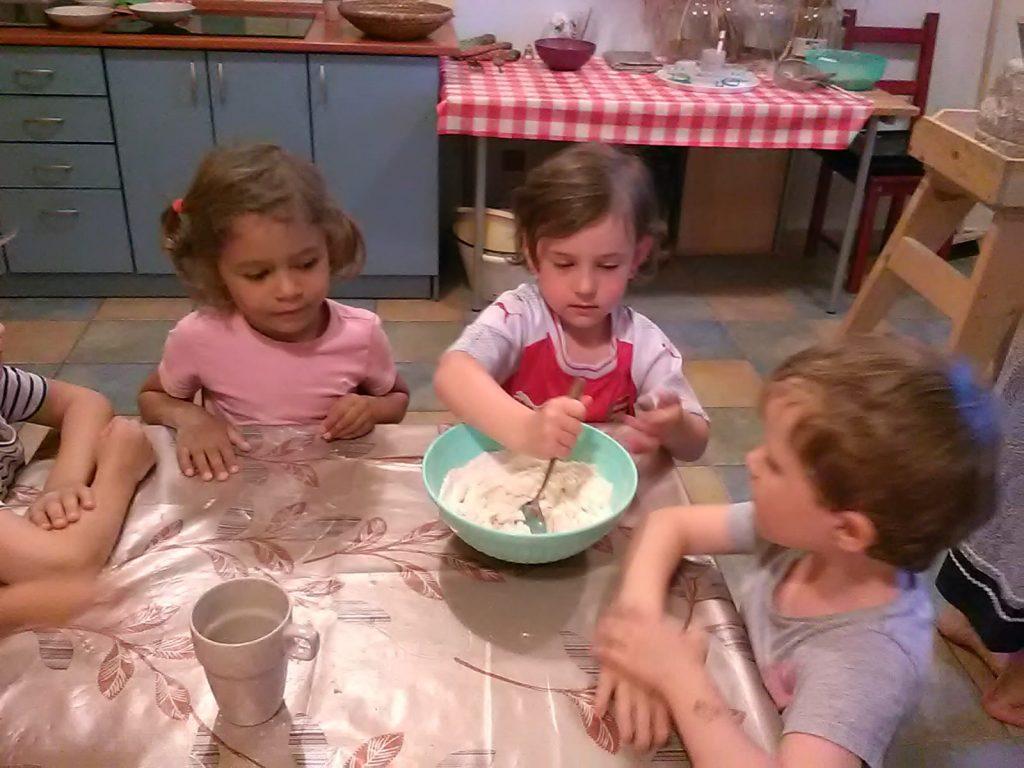 Děti sedí u stolu a holčička míchá těsto.