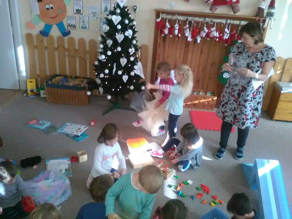 Děti rozbalují dárečky pod stromečkem ve školce.