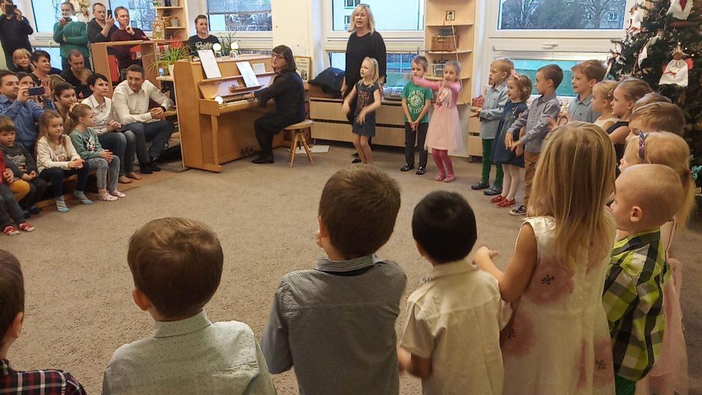 Představení dětí při vánoční besídce, Zpívají při klavíru.