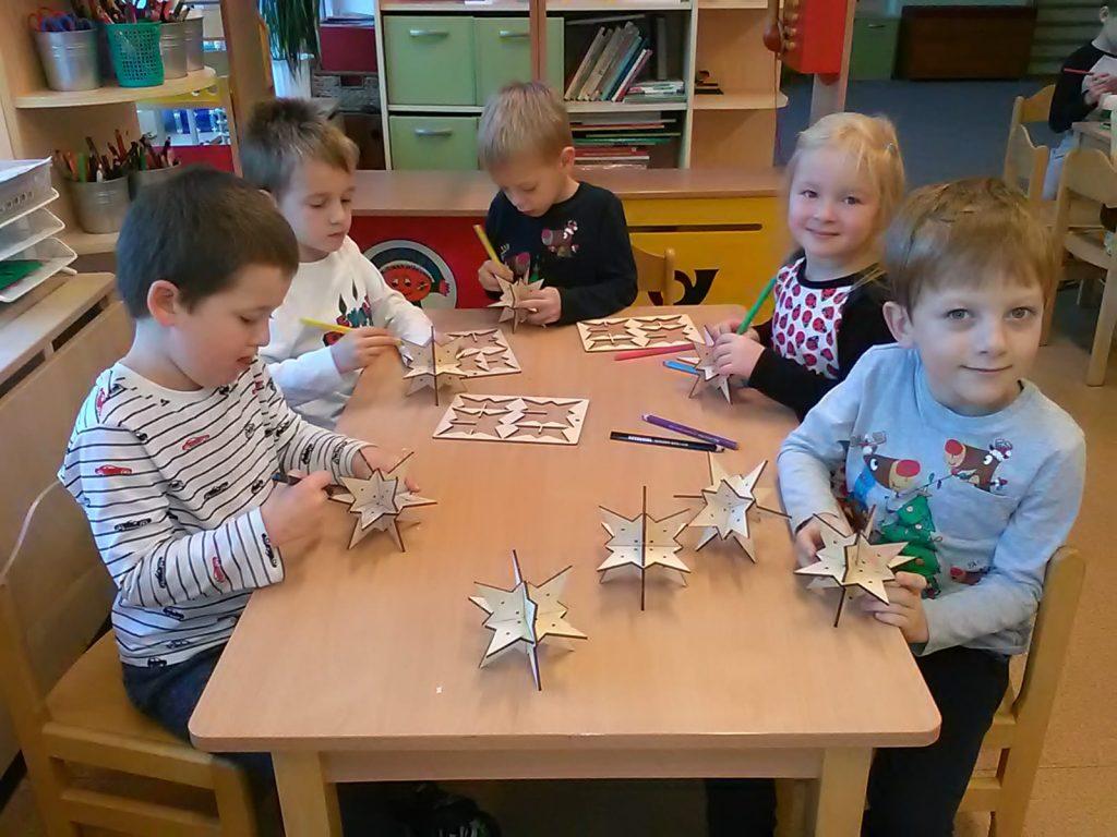 Děti vyrábějí vánoční dřevěné hvězdy.