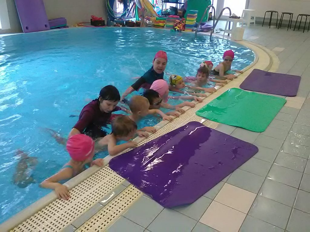 Děti se drží kraje bazénu.