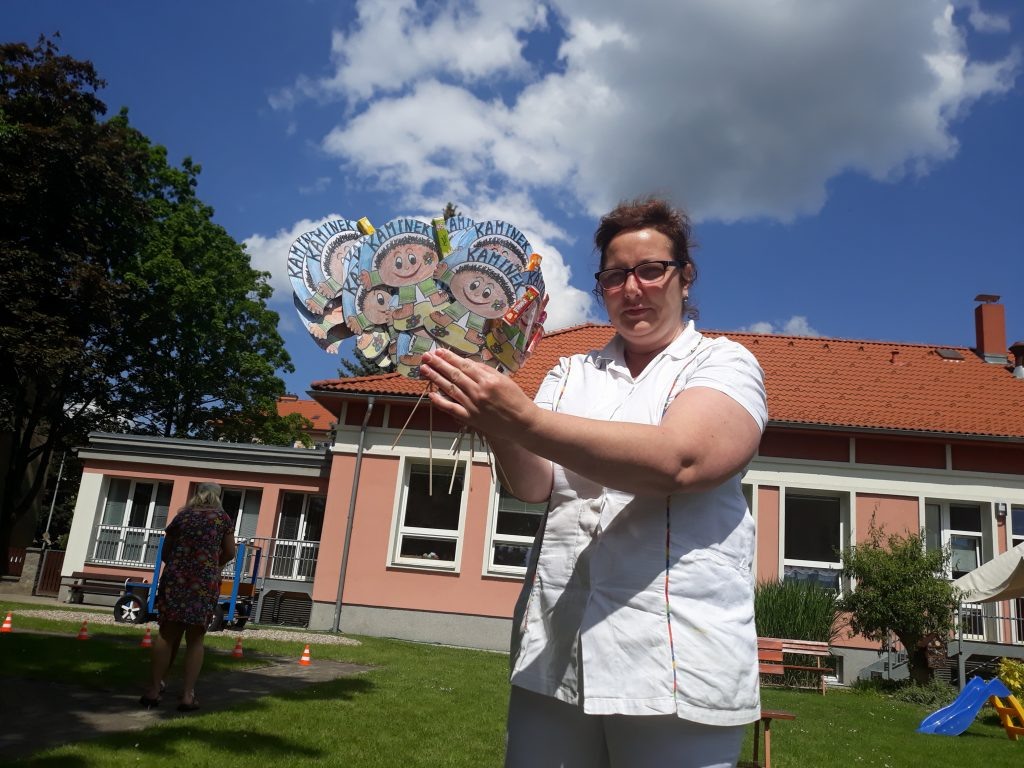 Paní kuchařka drží v ruce odměny pro děti.