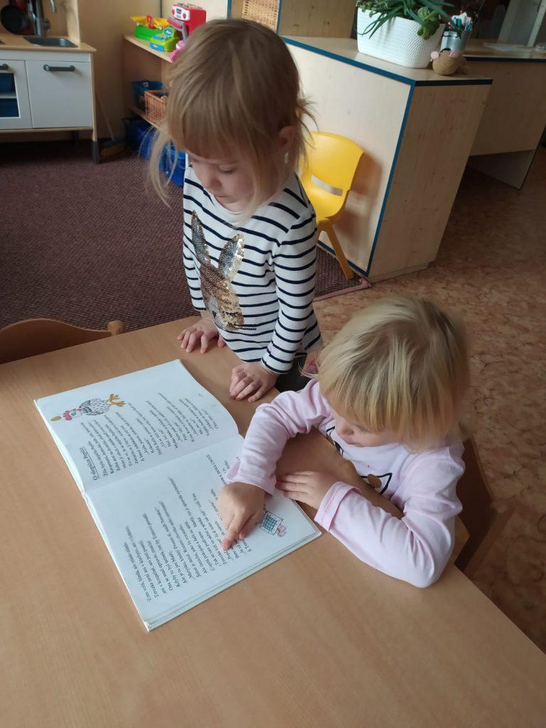 Děti si čtou v knížce.