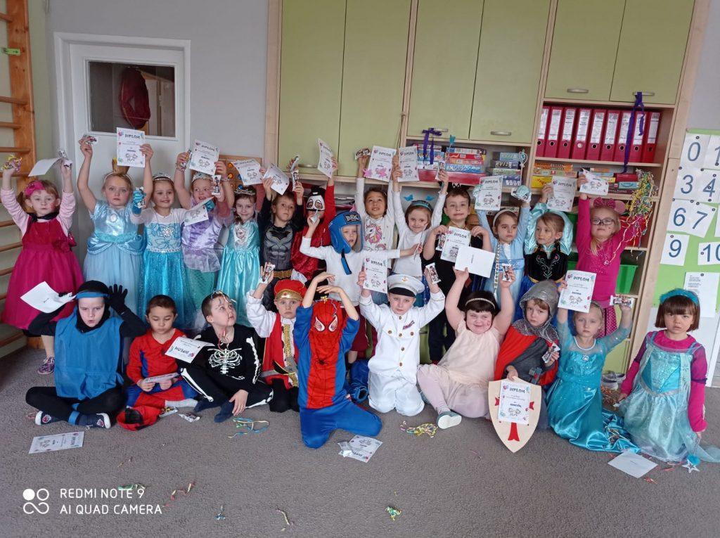 Děti v kostýmech ukazují diplomy.