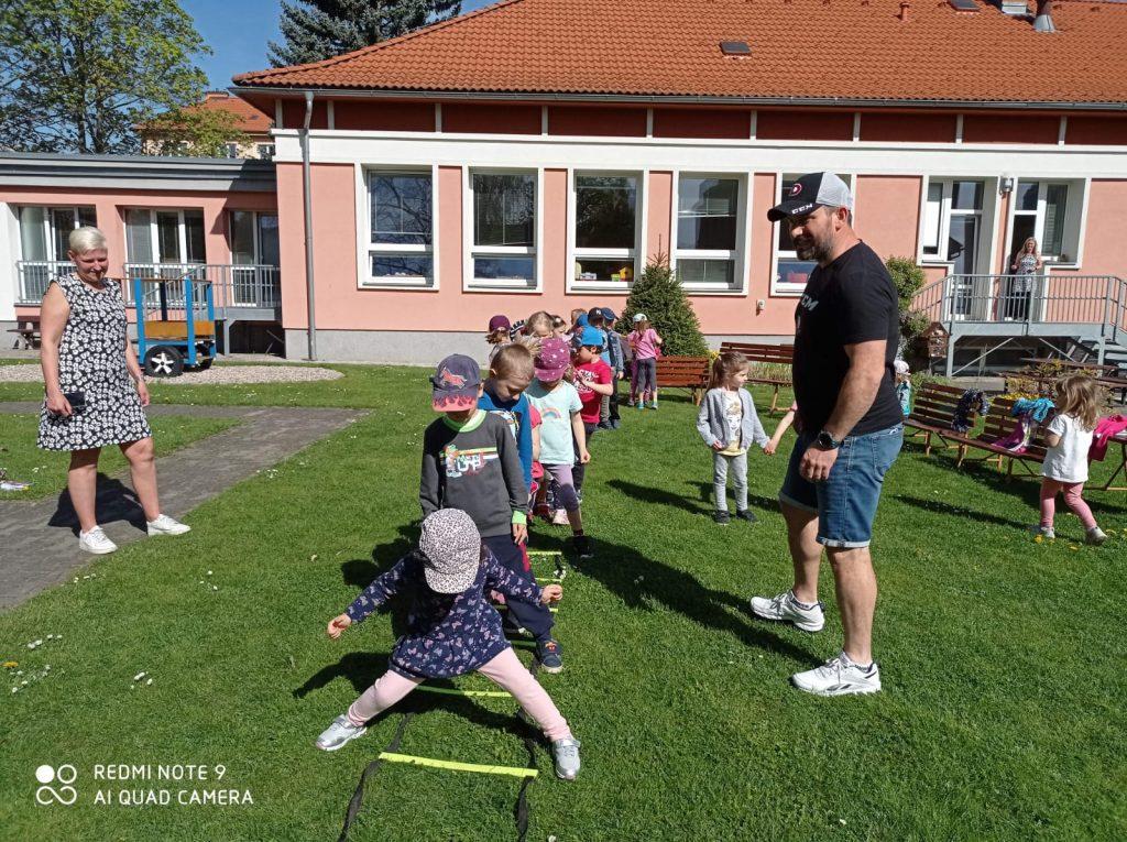 Děti cvičí na zahradě mateřské školy.