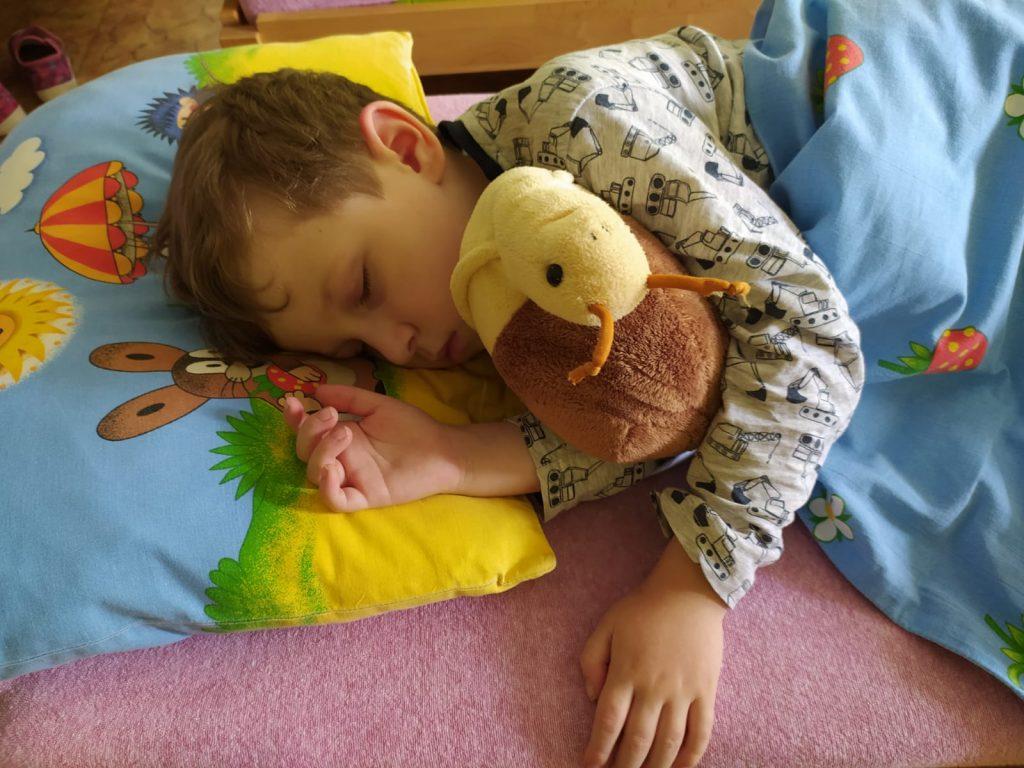 Chlapec spí v postýlce.