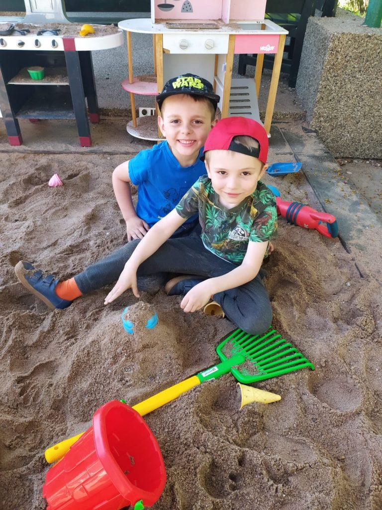 Kluci si hrají na písku.