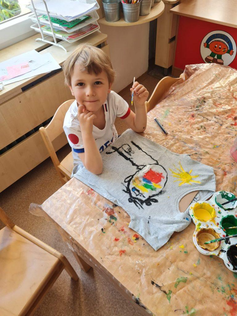 Chlapec maluje na tričko.