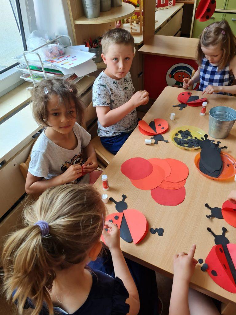 Děti tvoří z papíru berušku.
