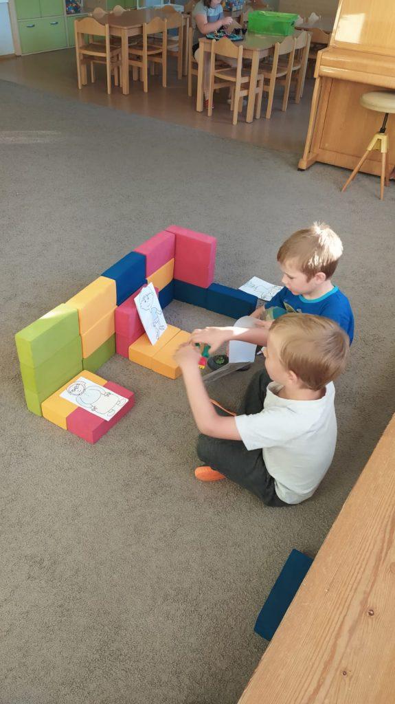 Kluci si hrají na koberci s kostkami.