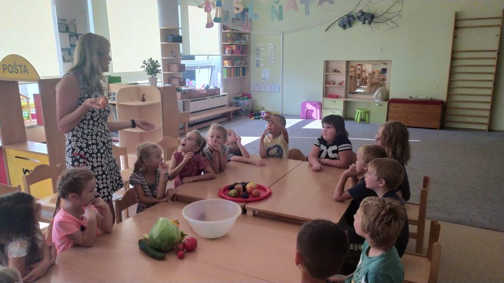 Děti sedí u stolu a povídají si o ovoci a zelenině.