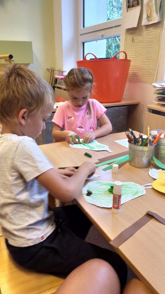 Děti tvoří u stolečku.