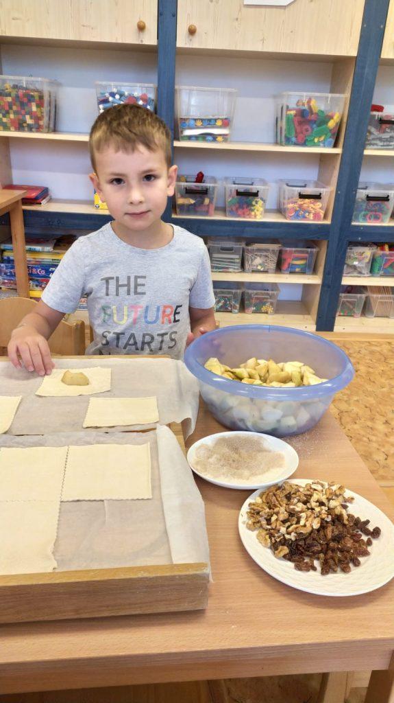 Chlapeček plní těsto na koláčky.