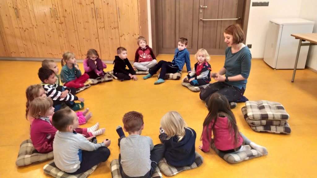 Děti sedí v kruhu a poslouchají povídání o zvířátkách.